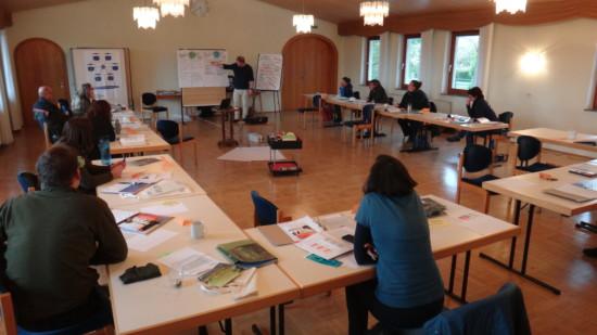 Seminarraum mit etwa 10 Personen an Tischen in U-Form und zeigende Person vorne an Pinnwand